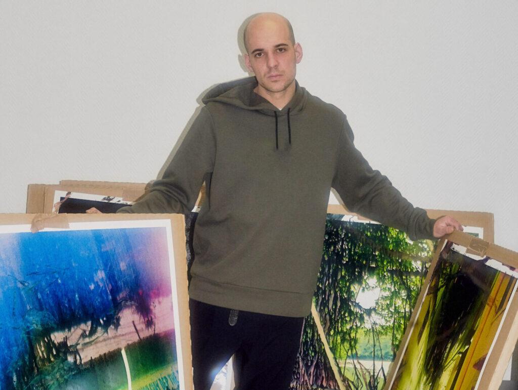 Fotograf Jean-Vincent Simonet mit Bildern im Atelier